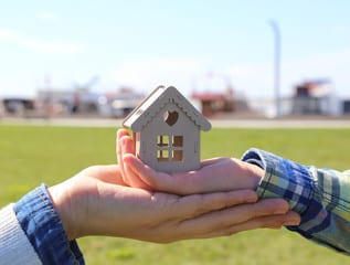 Toy house being held in some hands